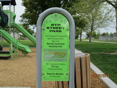 green sign in front of playground equipment