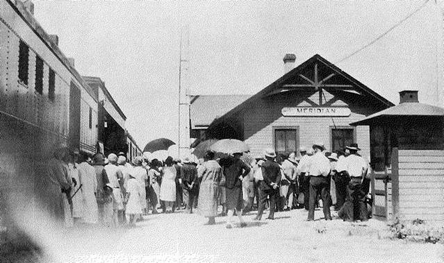 crowd of travelers waiting by a railcar