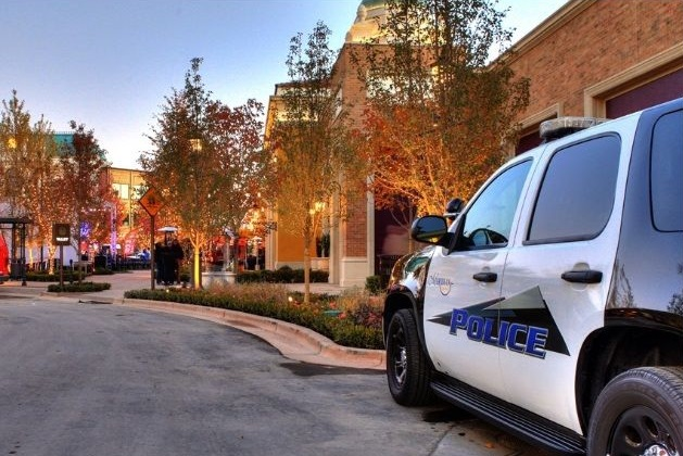police car against a backdrop of retail stores at the Village in Meridian