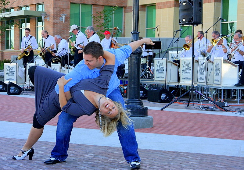 A man and woman dance in front of a band performing a concert