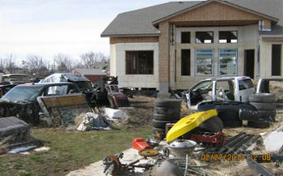Photo of house with large amounts of junk such as tires and vehicles in yard