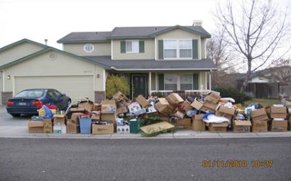Photo of dozens of boxes piled on sidewalk in front of a house