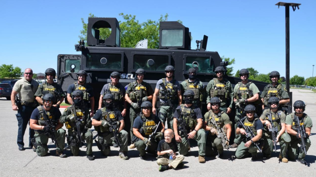 Group photo of Ada Metro SWAT officers in gear, in front of a SWAT vehicle.